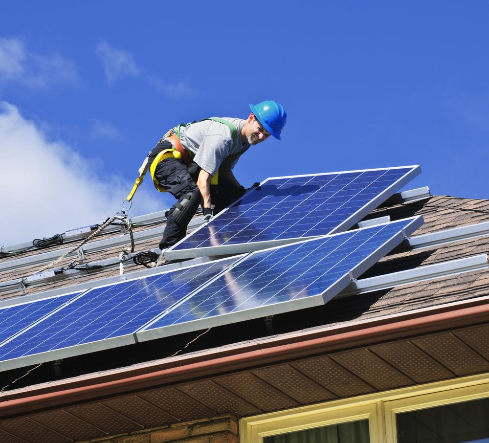 Arbeiter installiert Solar-Panels auf einem Dach
